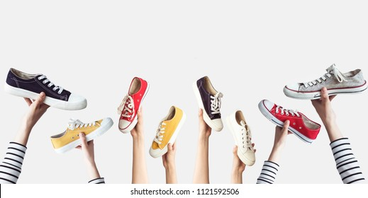 Hands holding colorful canvas shoes