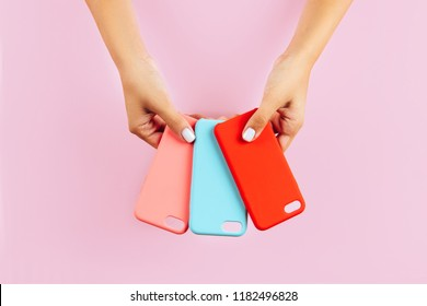 hands holding colorful smartphone cases. Pink Background