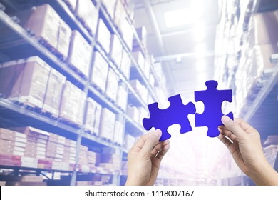 Hands holding connecting two piece blue jigsaw at warehouse background, team work concept.
