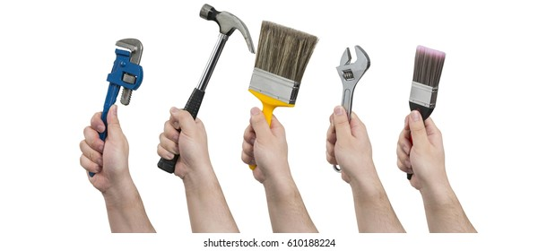 Hands holding construction tools including a pipe wrench, a hammer, paintbrushes, and an adjustable spanner