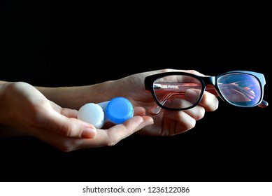 Hands holding contact lenses and glasses on a black background.