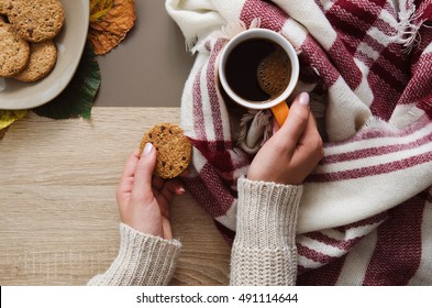 Hands holding cookie and coffee on wooden table with scarf on autumn time