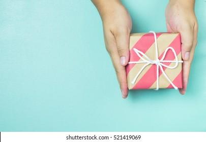 Kädet tilalla käsitöitä paperi lahjapaketti lahjaksi jouluksi, uusi vuosi, ystävänpäivä tai vuosipäivä sinisellä pohjalla, ylhäältä katsottuna