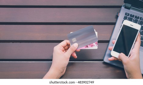 Hands holding credit card, smart phone and using laptop. Online shopping concept-vintage tone and flare filtered