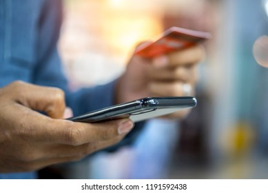 Hands holding credit card and using smartphone for payment online