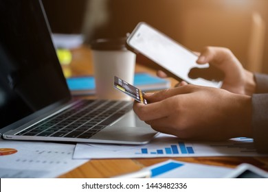 Hands holding credit card and using laptop and smart phone. Online shopping. Online payments concept.