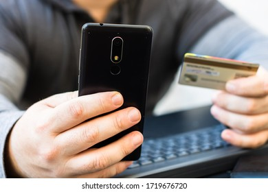 Hands holding credit card and using smartphone and laptop. Online shopping, on line payment concept