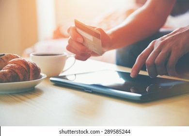 Hands holding credit card and using digital tablet pc with morning coffee and croissant. Online shopping.