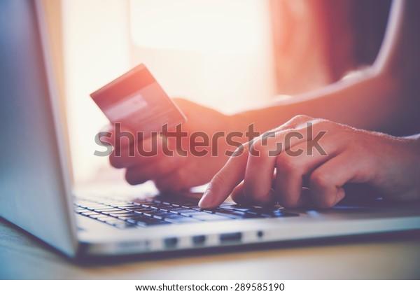 Руки держат кредитную карту и используя ноутбук. Онлайн-шопинг