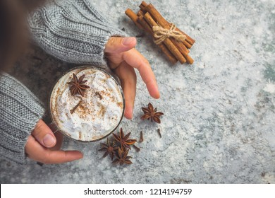 Hands holding cup of chai latte, toned