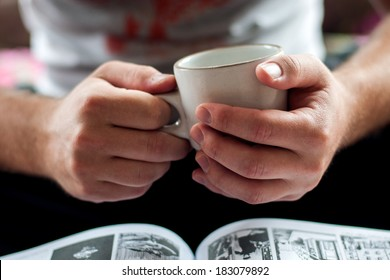 hands holding a cup of coffee