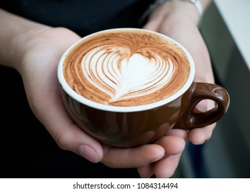 Hands holding a cup of coffee: mocha, caffe mocha