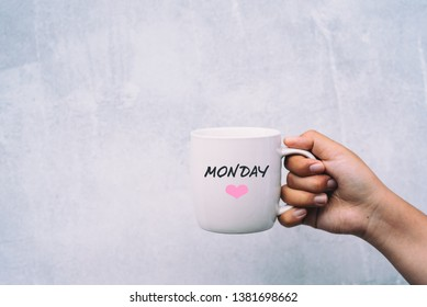 Hands holding cup of coffee with Monday Greetings and Pink Heart Shape