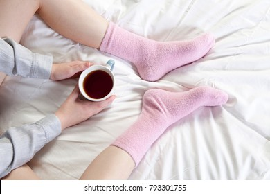 Hands holding a cup of coffee. You can see the legs in pink socks.