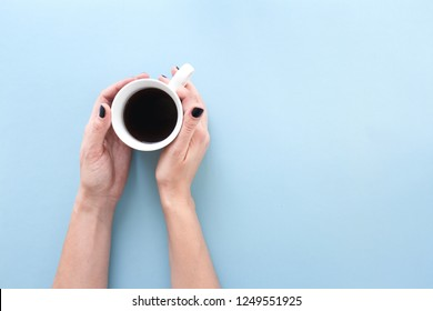 Hands holding a cup of freshly brewed black coffee, flat lay on blue background.