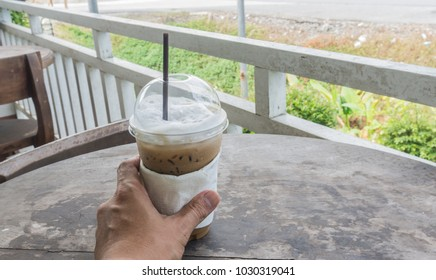 Hands holding a cup of ice coffee.