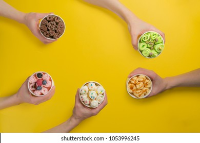 Hands holding cups with different rolled ice cream on bright yellow background
