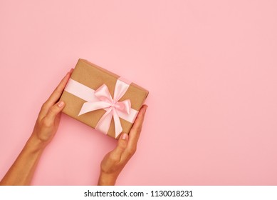 Hands holding cute gift box on pink flatlay