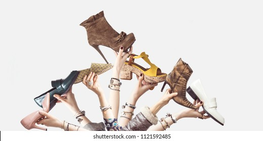 Hands holding different shoes on isolated background