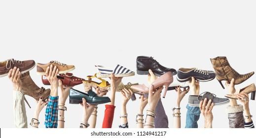 Hände, die verschiedene Schuhe auf isoliertem Hintergrund halten