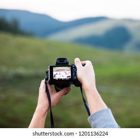 Hands holding the digital photo camera. Looking at the camera preview. Checking the playback screen. Mountain landscape in the background.