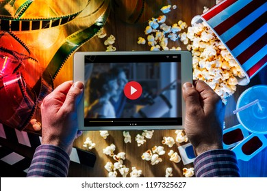 Hands holding a digital touch screen tablet with popcorn, 3D glasses and filmstrip; movie online streaming cinema and entertainment concept
