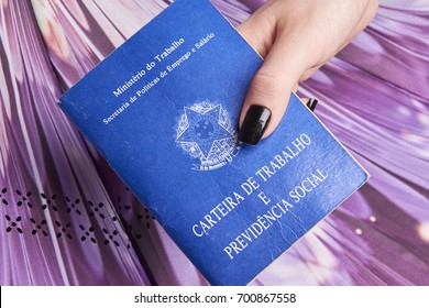 Hands holding a document work or Brazilian work books, social security or worker rights (Carteira de trabalho e Previdencia Social) in colorfull background.