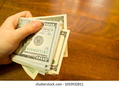 In the hands of holding dollars on a wooden background
