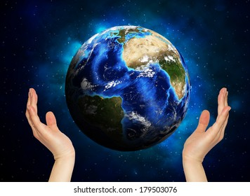 Hands holding earth. Starry sky in the background