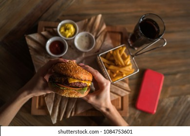 Hands holding fresh delicious burger with french fries, sauce and beverage on the wooden table top view. Tasty grilled home made burger with beef, tomato, cheese, cucumber and lettuce. Soft focus.