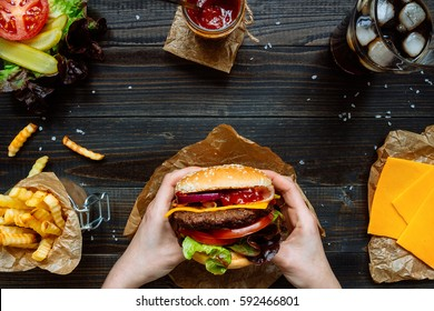 Hands holding fresh delicious burgers with french fries, sauce and beer on the wooden table top view.