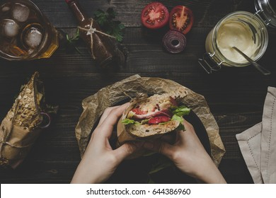 Hands holding fresh delicious submarine sandwiches on the wooden table. Top view.