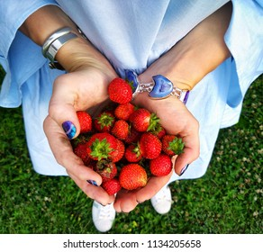 Hands holding fresh strawberries.Woman in blue dress with beautiful jewelry shows her summer harvest. Bright and colorful conception of gardening.