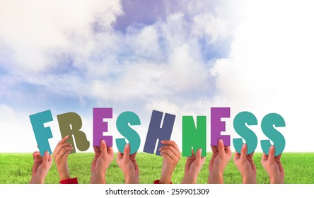 Hands holding up freshness against green field