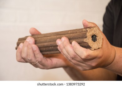 Hands holding fuel briquette. Wooden  briquettes are an environmentally friendly fuel source that are used to start a fire. They are made by pressing of dry sawdust.