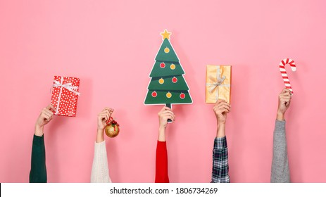 Hands holding gift boxes and colorful Christmas decorating items on pink isolated background