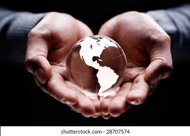 Hands holding a glass globe showing America continent