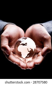 Hands holding a glass globe showing Africa, Europe and part of Middle East