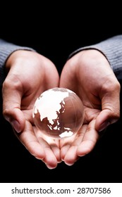 Hands holding a glass globe showing Asia and Australia continent