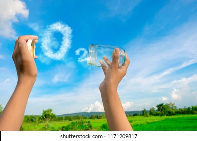 Hands holding glass jar for keeping fresh air, O2 cloud word with a blue sky in the background. concept of clean atmosphere, fresh air and a green environment.
