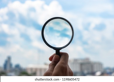 hands holding glass magnify against blue sky background. Business Explore, Searching, Discovery and Vision concepts