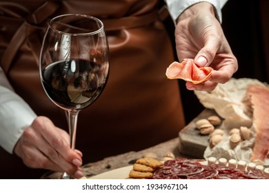 Hands holding a glass of wine and a wooden board with different kinds of cheese and ham, prosciutto, jamon salami, Antipasto Dinner or aperitivo party concept.
