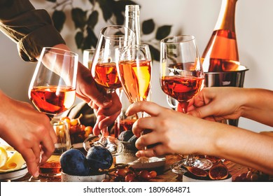 Hands holding glasses with rose wine over the table served for festive dinner party with different kinds of appetizers and fruits