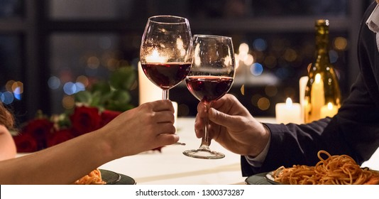 Hands holding glasses of wine on restaurant background. Let's have a toast concept
