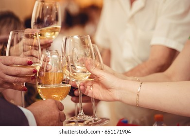 hands holding glPeople clinking glasses with wine and delicious dishes on tableasses and toasting, happy festive moment, luxury celebration concept