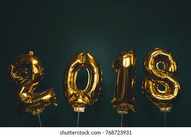 Hands holding golden 2018 balloons, new year concept