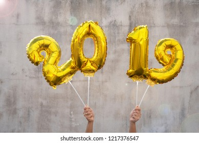 Hands holding golden 2019 balloons, new year concept