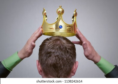 Hands holding a golden crown above a head. Award ceremony of winner. Self-proclamation concept.
