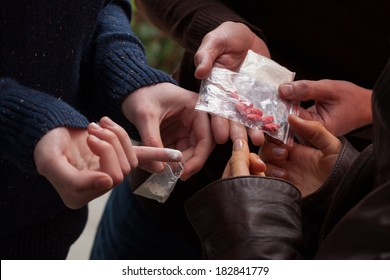 Hands holding grams and tabs of drugs