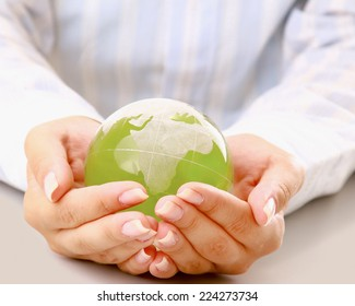 Hands holding a green earth, isolated on white background